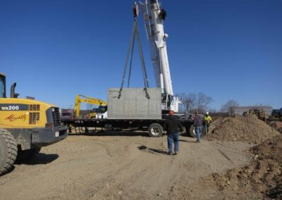 fabco industries stormsafe cartridge vault precast being moved by crane
